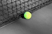 tennis ball against a black net
