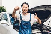 Professional Car Mechanic In Uniform Holding Car Key And Fixing A Car Engine And Repairing Checking  poster