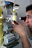 Electricista examinar una caja de fusibles con una antorcha