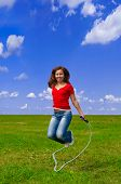 picture of jump rope  - Young woman with skipping rope on the lawn - JPG