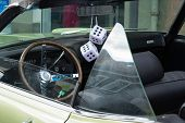 Fuzzy Dice On The Rearview Mirror Of A Vintage American Car poster