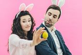 Young Couple On Pink Background. On The Head Is A Bunny Ears. The Wife, Having Amazed, Lifted Her Ey poster