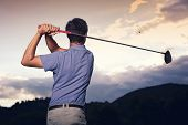 Close up of professional golf player in blue shirt teeing-off ball at sunset, view from behind.