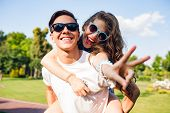 Portrait Of Cute Couple Having Fun In Park. Pretty Girl With Long Curly Hair Is Riding On Back Of Ha poster