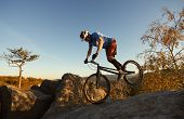 Athletic Cyclist Riding On Front Wheel On Trial Bike. Professional Sportsman Rider Making Acrobatic  poster
