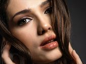 Beautiful woman with brown hair. Attractive model with brown eyes. Fashion model with a smokey makeu poster