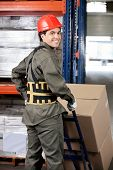 Portrait of young warehouse worker pushing handtruck with cardboard boxes