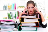 image of frustrated  - tired business woman with documents in her workplace - JPG