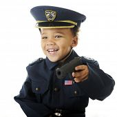 Closeup image of a delighted preschooler wielding a toy guy in his policeman uniform.  Motion blur on hand and gun.  On a white background.