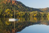 image of winona  - Fall color trees and a reflective lake with a sailboat - JPG