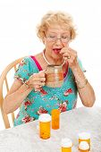 Healthy senior woman taking her daily doses of medicine.  White background.
