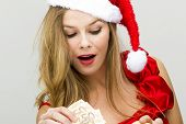 Young woman in Santa hat holding piggy bank and money on neutral background.