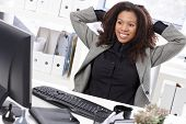 Beautiful afro businesswoman sitting at desk in office, smiling, stretching.