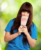 girl looking through empty popcorn packet, outdoor