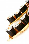 served sushi rolls on small bamboo boat