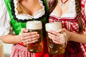image of stein  - Two young women in traditional Bavarian Tracht in restaurant or pub with beer and beer stein - JPG