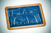 sentence feliz navidad, merry christmas in spanish, written with chalk in a blackboard