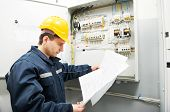 stock photo of voltage  - Electrician builder at work inspecting cabling connection of high voltage power electric line in industrial distribution fuseboard - JPG