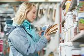 Young woman choosing paint using color samples during hardware shopping in home improvement store su