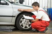 stock photo of inspection  - mechanic repairman inspecting car body during automobile car maintenance at auto repair shop service station - JPG