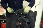 Professional auto mechanic balancing wheel before changing it