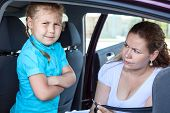 Mother Convincing A Girl To Get In Child Safety Seat Against The Wishes