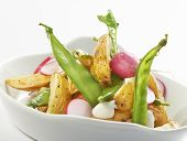 close up of a delicious potato salad with raddish and sugarsnaps