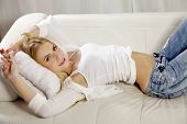 Beautiful and attractive young adult smile blonde woman posing in blue jeans and white shirt sweater