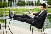 Young successful businessman relaxed outdoors with tablet