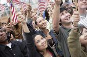 Постер, плакат: Группа многоэтнических людей подняв американские флаги