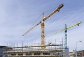 stock photo of scaffolding  - several cranes on a construction site with scaffolding - JPG