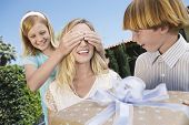 Daughter covering mother's eyes as son holds a gift in front of her