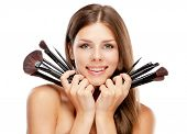 Beautiful woman holding makeup brushes, isolated on white background