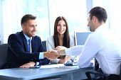 stock photo of joining hands  - businessman shaking hands to seal a deal with his partner - JPG