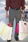 Low section of a man standing with shopping bags outdoors