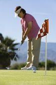 Постер, плакат: Вид сбоку среднего возрасте женщины игра в гольф