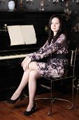 Beautiful Young Woman In Dress Sit At Black Old Piano With Music.