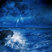 Image of night stormy sea with big waves and lightning