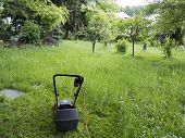 foto of grass-cutter  - Mower and garden overgrown with weeds  - JPG