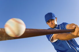 pic of bat  - Baseball player hitting the ball with a bat against clear blue sky - JPG