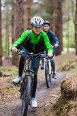 Girl and boy biking on forest trails