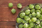 fresh Brussels sprouts in a metal steamer basket on red wooden rustic table