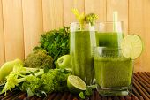 Glasses of green vegetable juice and vegetables on bamboo mat on wooden background