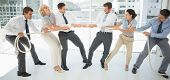 image of tug-of-war  - Full length of a group of business people playing tug of war in office - JPG