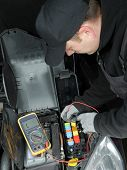 Auto mechanic checking car fuses using multimeter