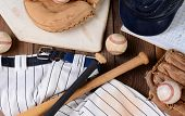 High angle shot of baseball gear on a rustic wood surface. Items include, Home Plate, helmet, baseball, ball, glove, catchers mitt, score book, pants, belt and bats.