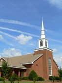 pic of fundamentalist  - Vertical church with tall white steeple against blue sky - JPG