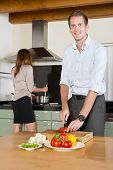 Ambitious couple, smartly dressed, preparing dinner after coming home from work
