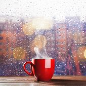 image of raindrops  - Steaming cup of coffee over a cityscape background - JPG