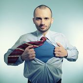 Super hero. Business manopening his shirt like a superhero, over blue background